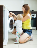 Woman with toddler using washing machine
