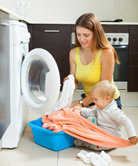 Family woman putting clothes in to washing machine
