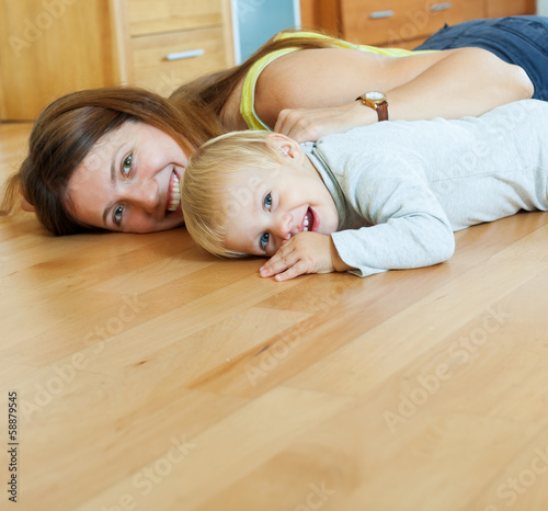 happy mom and child on wooden floor