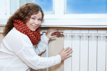 Woman in warm clothes checking temperature of heating radiator