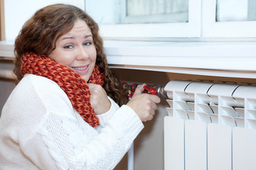 Young woman feels cold when turning thermostat of radiator