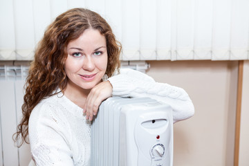 Woman sitting near radiator trying to heat up in domestic room
