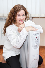 Portrait of long-haired curly woman near oil heater at her home