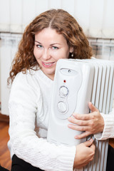 Woman embracing white oil heater sitting on domestic  floor