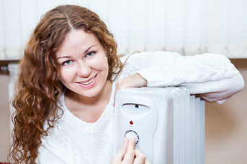 Caucasian woman controlling temperature of oil heater