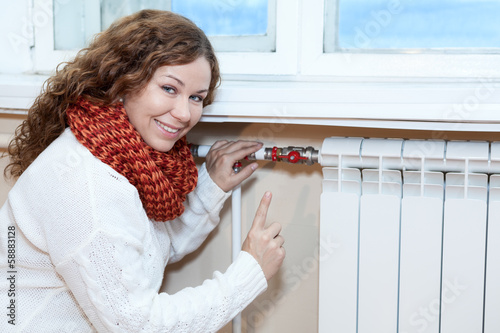 Happy woman gesturing when controling thermostat on radiator