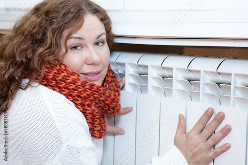 Young woman leaning to convector for warming hands