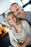 Cheerful senior couple enjoying fireplace in winter