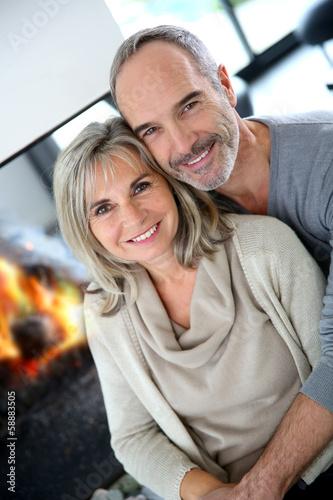 Cheerful senior couple enjoying fireplace in winter