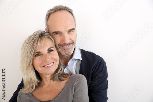 Cheerful senior couple standing on white background