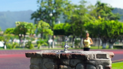 A young woman running and drinking from a water faucet