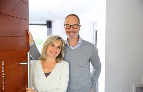 Senior couple welcoming people to enter home - 58883702