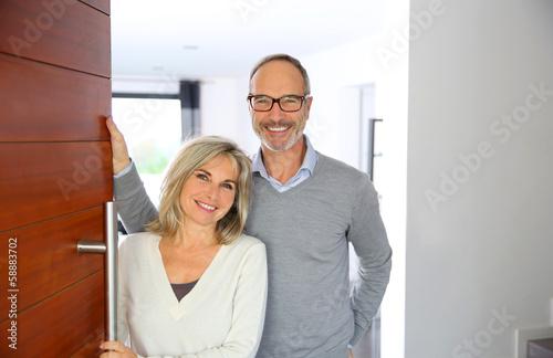 Leinwanddruck Bild Senior couple welcoming people to enter home