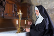 Nun lighting altar candles