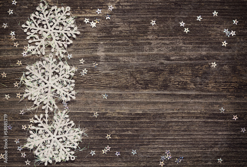 Snowflakes and stars on wooden background