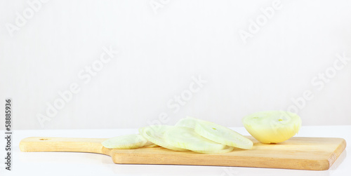 Fresh sliced raw onion on a wooden cutting board closeup