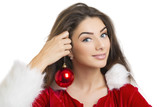 Pretty Santa girl having fun with red Christmas ball as earring