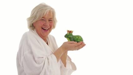 senior woman kisses a frog