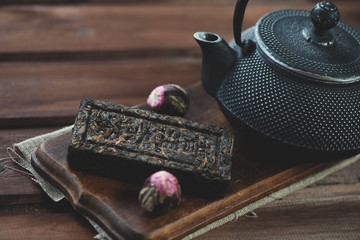 Compressed herbal tea and tetsubin teapot, wooden background