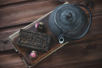 Above view of herbal tea and cast-iron teapot on a cutting board
