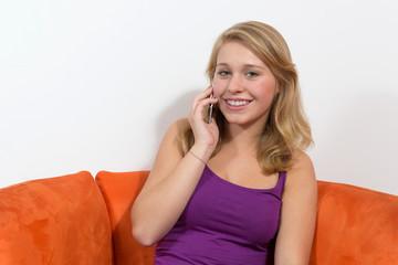 Junge Frau lächelnd beim Telefonieren