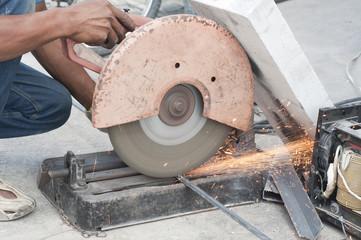Worker cutting steel bars.