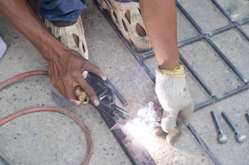 Worker welding steel bars.