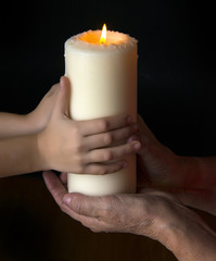 old hands and baby hands holding a candle - concept