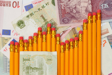 Graph of pencils against background of yuan and euro banknotes