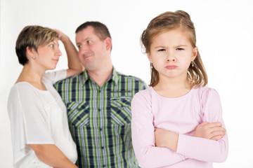 Beleidigtes Kind, genervte Eltern im Hintergrund