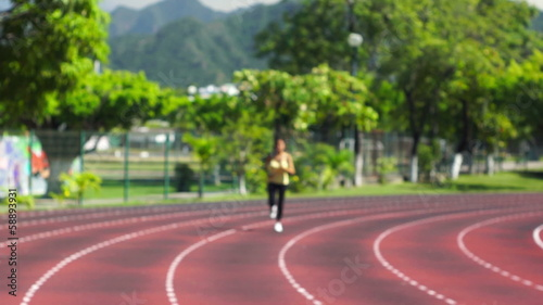 A young woman running at a track in a stadium
