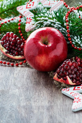 Pomegranate and apple with festive decorations