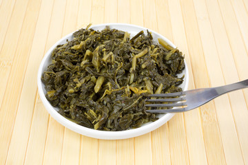 Serving of collard greens in a dish with fork