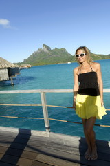 Woman on deck of overwater bungalow at resort
