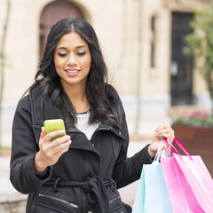 Smiling woman reading message and holding shopping bags.