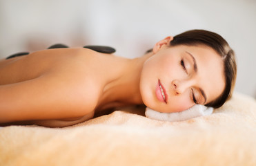 beautiful woman in spa salon with hot stones