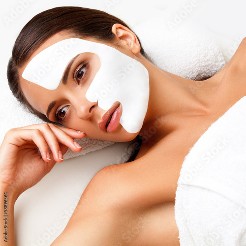 Young Woman at Spa Salon With Cosmetic Mask on Face.