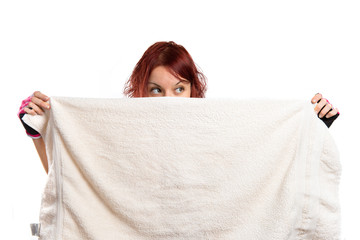 Young girl hiding behind a towel.