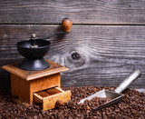 Manual coffee grinder with beans and vintage scoop on wooden bac