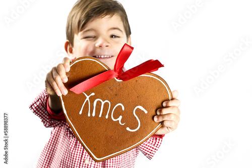 Leinwanddruck Bild Junge zeigt Lebkuchenherz
