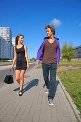Girl and Boy walking down the sidewalk, girl showed tongue