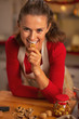 Happy young woman eating walnuts in kitchen