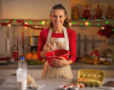 Happy housewife whisking dough in christmas decorated kitchen