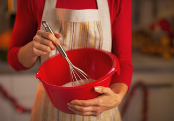 Closeup on young housewife using dough whisk