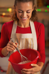 Happy young housewife using dough whisk
