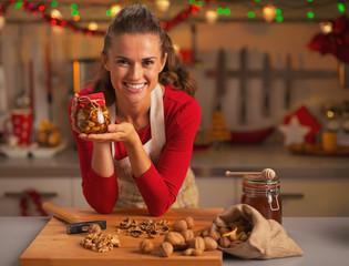 Happy young housewife showing jar with honey nuts