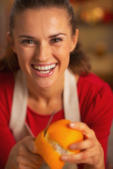 Portrait of happy young housewife removing orange peel