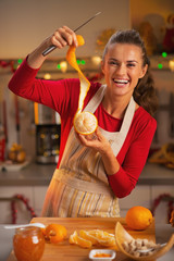 Happy young housewife showing orange peel in kitchen