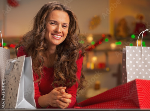Happy woman with shopping bags in christmas decorated kitchen