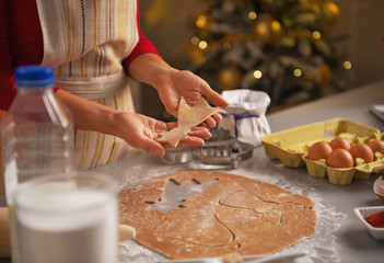 Closeup on young housewife making christmas cookies in kitchen